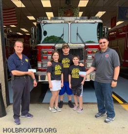 Holbrook FD Chief Bodor and 2nd Assistant Chief Monthie with Lila, Jake, and Bret Auricchio
